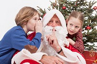 Boy wispering in Santa Claus ear