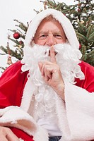 Santa Claus with finger on lips, smiling, portrait