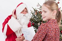 Girl reading list while Santa Claus listening