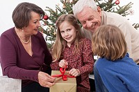 Grandchilds opening Christmas gift with grandparents