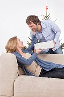 Woman leaning on couch and receiving gift from man, smiling