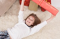 Boy lying on back and holding Christmas gift, smiling, portrait