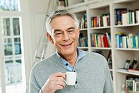 Germany, Berlin, Senior man with coffee cup, smiling, portrait
