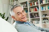 Germany, Berlin, Senior man on couch, portrait