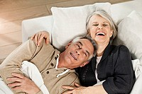 Germany, Berlin, Senior couple lying on couch, smiling