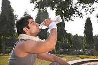 Young man with towel round shoulders drinking water after workout