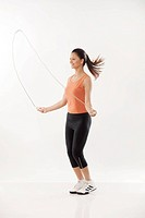 Full length of a young woman exercising with a jump rope over white background