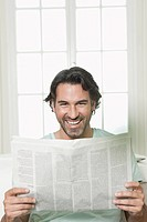 Germany, Berlin, Mature man with newspaper, smiling, portrait