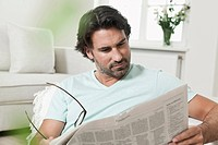 Germany, Berlin, Mature man reading newspaper
