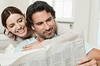 Germany, Berlin, Mature couple reading newspaper, smiling