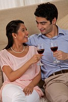 Relaxed young couple holding wineglass together at home