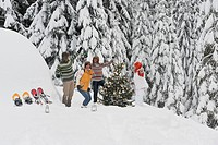 Austria, Salzburg, Men and women dancing by christmas tree in winter
