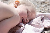 Germany, Bavaria, Girl lying on beach towel, smiling, close up