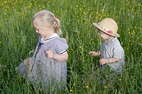 Germany, Bavaria, Girl and boy walking through meadow