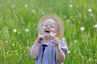 Germany, Bavaria, Girl with dandelion seed, smiling (thumbnail)