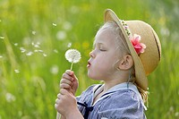 Germany, Bavaria, Girl blowing dandelion seed