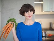 Germany, Cologne, Young woman with carrots in kitchen, smiling, portrait