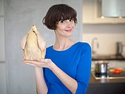 Germany, Cologne, Young woman with raw chicken in kitchen, smiling, portrait