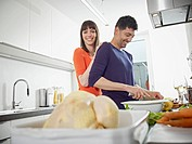 Germany, Cologne, Man and woman cooking together in kitchen