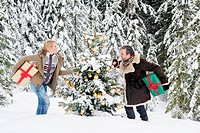Austria, Salzburg County, Couple holding christmas gift in snow, smiling