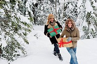Austria, Salzburg County, Couple holding christmas gift and walking in snow
