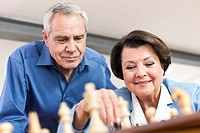 Germany, Leipzig, Senior man and woman playing chess game, smiling
