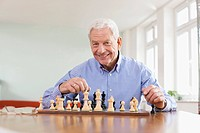 Germany, Leipzig, Senior man playing chess game (thumbnail)
