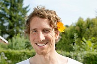 Germany, Hamburg, Man wearing marigold in allotment garden