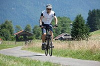 Germany, Bavaria, Young man cycling through country road