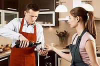 Young couple drinking wine while preparing meal