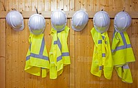 Hard hats and safety vests with reflective stripes, safety workwear, hanging on a panelled wooden wall. Workplace
