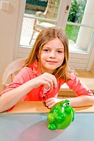 Girl dropping coins into piggy bank.