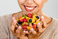 Woman eating fruit salad.