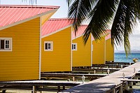 Yellow waterfront cabins at El Faro del Colibri hotel on Isla Carenero, Bocas del Toro Archipelago, Panama