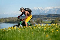 Cyclist on an electric bicycle in front of Tachinger See lake, Chiemgau region, Upper Bavaria, Bavaria, Germany, Europe
