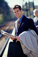 Smiling Businessman on Railroad Platform