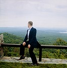 Man on Guardrail Overlooking Forest