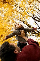 Father Playing with Daughter Under Autumn Trees