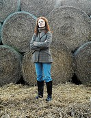 Young Woman Standing in Front of Straw Bales