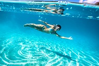 young woman swimming underwater in turquoise lagoon