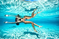 young woman floating in crystal clear turquoise lagoon