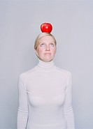 Young woman balancing an apple on her head