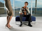 Young Man Sitting on Footstool Looking at Woman