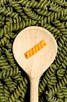 Yellow noodle on wooden spoon amongst green noodles