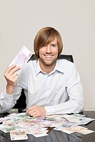 Happy man at desk with Euro notes