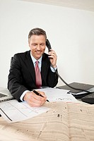 Smiling manager with newspaper on the phone at desk