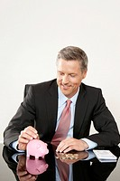 Businessman putting coin into piggy bank
