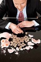 Businessman with broken piggy bank counting coins