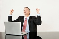 Cheering businessman with laptop