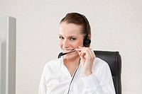Smiling young woman wearing headset in office